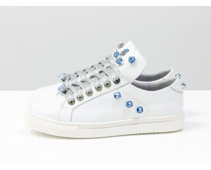 Нарядные Кеды из натуральной кожи ярко-белого цвета, которые украшены сверкающими камнями ярко-голубого цвета и металлическими кольцами серебряного цвета, на утолщенной белой подошве и с яркой серебряной шнуровкой, Т-17409-02