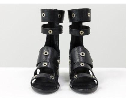 Удобные яркие босоножки гладиаторы на невысоком каблучке, выполнены из натуральной  кожи черного цвета и украшены серебряной фурнитурой с камнями, С-1816/И1-01